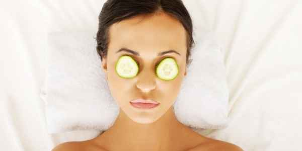 Cucumber slices placed on a womans eyes being used as a natural home remedy for puffy eyes.